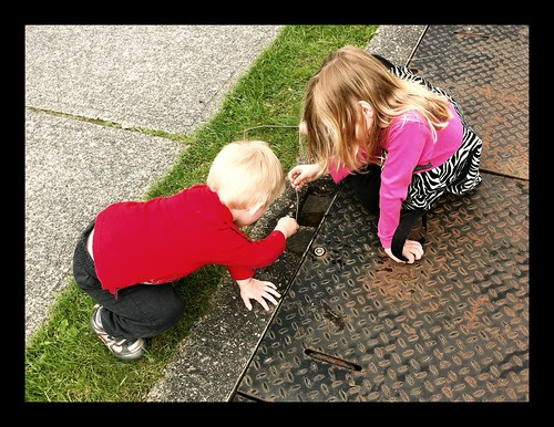 Playing on a manhole cover