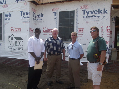 Standing in front of a home at the Crescent Shores Subdivision are left to right:  Dale Dukes, owner, Dukes Lumber Company; Steve Reynolds, owner, Drywall Complete; Jack Tarburton, USDA Rural Development State Director; and David Moore, CEO and President of Milford Housing Development Corporation.
