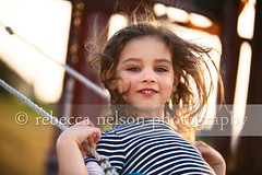 Portrait of a Happy Girl Swinging (Rebecca812) Tags: family sunset portrait motion cute girl beautiful smile grass fun outside happy kid day child play action stripes teeth joy daughter swing swingset ropes excitement onthemove playstructure brownhair canon5dmarkii rebecca812 heritage2011