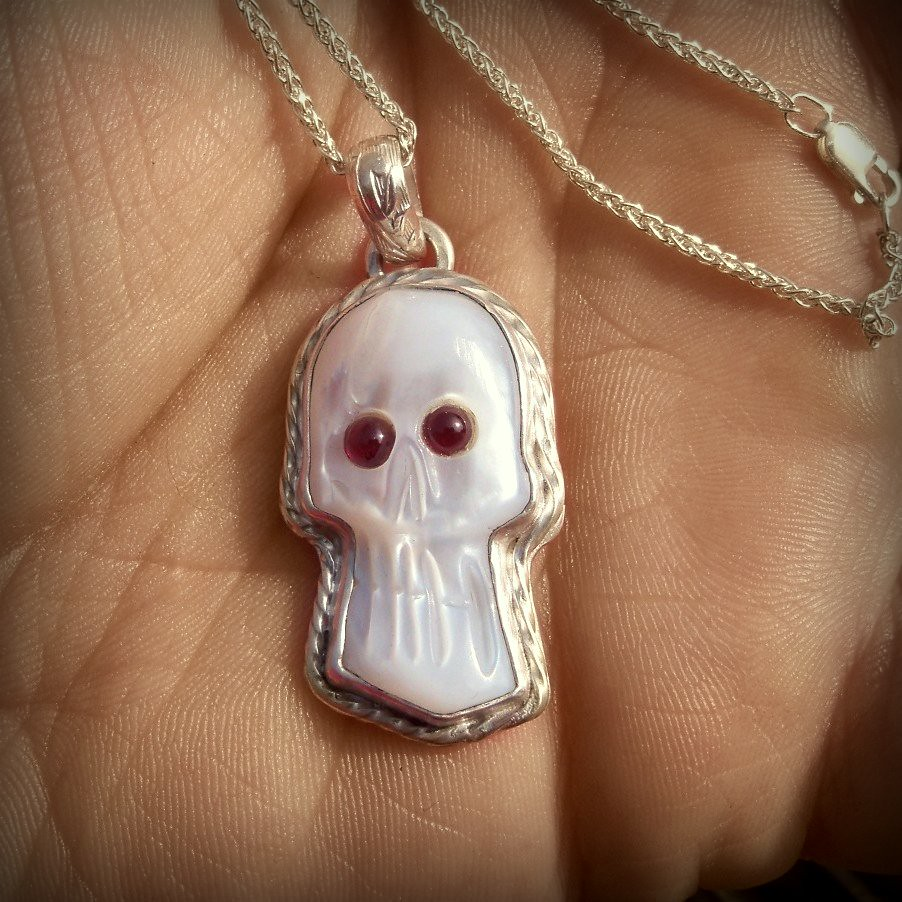 Black Bart mother of pearl Skull Cameo with garnet eyes set in sterling silver Pendant .