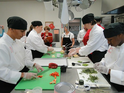 High school Culinary Arts students and Amy Lee, Culinary Arts Instructor and Recipe Team member, utilize their knife skills to chop vegetables during the recipe demonstration for the judging team.