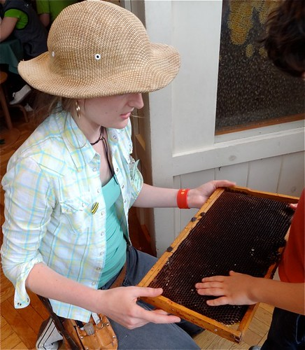 Janine lets a visitor touch the comb from a real beehive