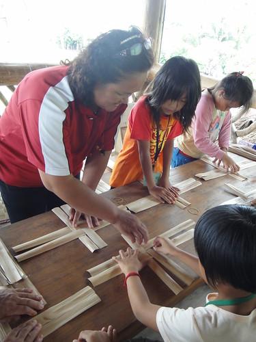 拿起處理過的月桃葉鞘, 學生們耐著性子學著編織餐墊
