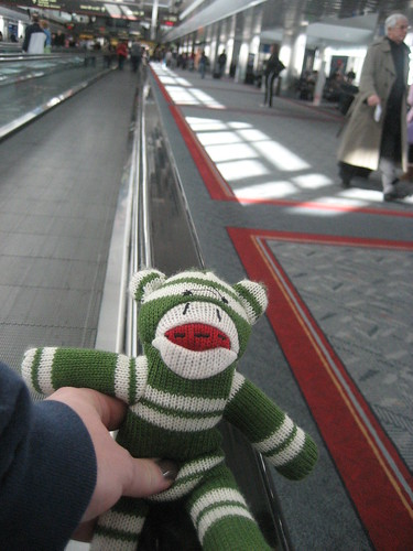 Sock Monkey rides the moving walkway