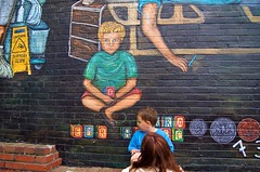 Regina Places her son next to his image in the mural 1