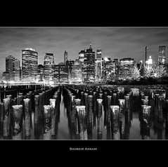 Manhattan At Night (Shobeir) Tags: nyc newyorkcity longexposure blackandwhite bw ny newyork skyline brooklyn night skyscraper landscape downtown cityscape manhattan brooklynheights financialdistrict highrise eastriver newyorkskyline newyorkatnight brooklynbridgepark woodenpost sigma1020 nikond90 shobeiransari silverefexpro
