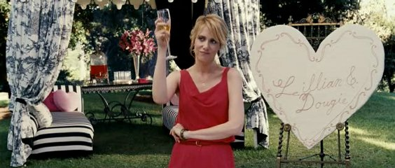 Kristin Wiig, wearing a red dress, makes a toast