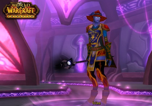 A draenei shaman with purple skin and glowing eyes wears her drinking hat, a tabard, pauldrons, a belt, long stocking-like leg coverings, and what appears to be a red pair of underpants. She is wielding a magical staff.