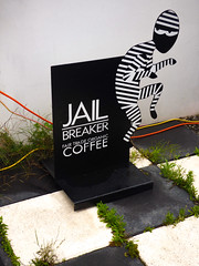 Jail Breaker (Steve Taylor (Photography)) Tags: jailbreaker fairtrade organic coffee ninja prisoner creeping wires cable art design sign blackandwhite yellow orange red tile metal man newzealand nz southisland canterbury christchurch cbd city stripes checkered