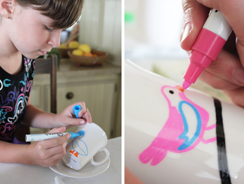 kid making art with markers on a cup