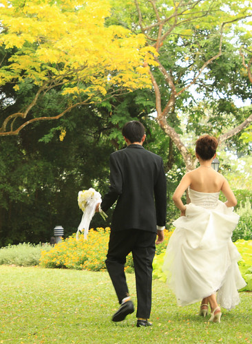 A bride and groom running through a green park in the summer