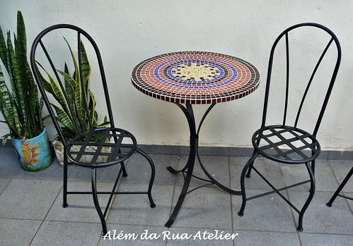mesa em mosaico e cadeiras de ferro