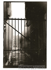 alley (laurast6) Tags: blackandwhite bw snow fog darkroom 35mm fence alley gate pentax smoke fisheye chain fireescape overtherhine pentaxspotmatic