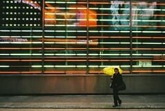 give me shelter (ho_hokus) Tags: nyc newyorkcity newyork rain yellow umbrella neon manhattan flag 35mmfilm timessquare gt raining minox compactcamera minox35gt givemeshelter filmphotographypodcast ny2011