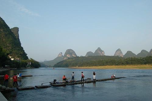 Vor einer Kette vom Karstbergen im Hintergrund ist der Yulong Fluss. Im Vordergrund steigen gerade Passagiere von den Bambussflössen.