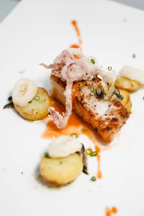 Pan Roasted Dory with mexican Romesco sauce served with Potatoes Fondant, Olives, Calamari and Nori Salt