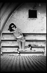 Revolving Stairs (Idalianie Flores Photography) Tags: bw flores cute film girl sunglasses stairs speed canon photography nicole exposure kodak 26 ae1 sandals cigarette trix iso professional drain 80s 400 shorts ida vignette sanchez isales idalianie