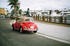 (fivefortyfive) Tags: trees red film girl car sunglasses vw 35mm bug volkswagen balloons bay pier boat little kodak hannah palm 200 1967 boardwalk minoltax370 fivefortyfive ithink timwalker maggieannre