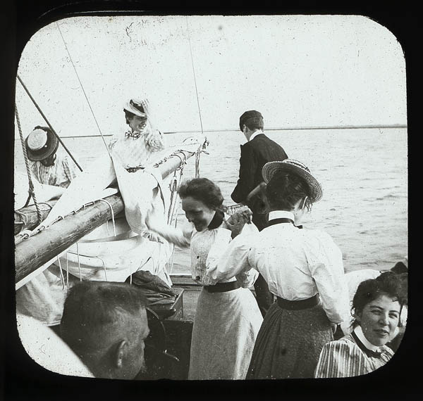 """Yachting."" View from the center of a boat, across the bow, with the sail down around the boom. Several women in Edwardian dress on different parts of the boat, while a man with his back to the camera faces the water, looking down. Photograph by T.S. and R.C. Stewart. Collection labeled ""Medical School Donations,"" possibly from the collection of the Carpenter family. Penn Museum image #218711"