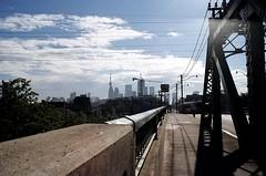 Hazy TO and Commuters (Georgie_grrl) Tags: bridge sky toronto ontario skyline clouds downtown cyclist shadows cntower ttc silhouettes