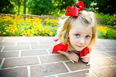 Lil' Blue Eyes (lunahzon) Tags: sc fun shadows redribbon bokeh naturallight greenery daytime playful yellowflowers lyingdown redbow childphotography rockhill bigblueeyes sillypicture kidportraits glencairngardens charlottearea lunahzonphotography