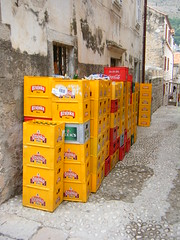 Dubrovnik, Croatia - empty beer crates outside a bar (rossendale2016) Tags: collection awaiting abandoned left dumped piled guards security windows bars inside indoor chairs tables meals seating intoxicants selling cafe restaurant sale fruit juice lager alcohol alcoholic handle handles carrying partitions transport corrugated tins glass street steep high colourful outside drinks soft cans bottles stacked stacking plastic ozujsko pivo cola coca coke necks yellow red bar beer empty crates croatia dubrovnik