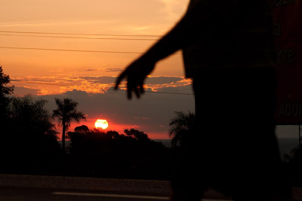 """Un Peregrino sube la colina en la tarde del 7 de Diciembre mientras baja el Sol, faltando poco para llegar al """"Curuzú Peregrino"""" que está en la entrada de Caacupé, muchos caminantes se quedaron a descansar en esta parte debido a la agotadora pendiente de la Ruta 2. (Elton Núñez - Caacupé, Paraguay)"""