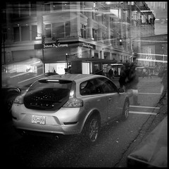 4:04 pm, Seymour & Georgia (Eric Flexyourhead (YVR catch-up mode!)) Tags: street city people urban bw canada motion blur cars vancouver corner walking volvo blackwhite movement downtown cityscape bc traffic doubleexposure britishcolumbia 11 66 multipleexposure pedestrians intersection hbc westgeorgia hudsonsbaycompany seymourstreet c30 volvoc30 olympusep1 panasoniclumix20mmf17