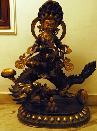 Arya Dzambala riding a dragon, holding wish fulfilling jewels, jewelry spitting treasury mongoose, hallway of a business, Boudha, Kathmandu, Nepal by Wonderlane