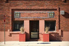 Exchange State Bank doorway (Studiobaker) Tags: studiobaker minnesota mn southeastern se october 2010 fall autumn autumnal imagery oct grand meadow grandmeadow small town drive explore exchange state bank building architecture architectural architect red brown brick purcell william george elmslie prairie school style artistic structural design terracotta terra cotta mosaic entrance door doorway symmetry symmetrical stop sign sidewalk wall exterior sun sunny outside shadow rectangle square rectangular lines solid stolid