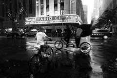 Radio City Corner (Airicsson) Tags: street new york city nyc summer urban blackandwhite bw usa white ny black rain island lumix us walk manhattan panasonic rainy cycle radiocitymusichall 2010 streetshot rockfellercenter blackwhitephotos lx3