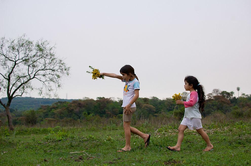 Alejandra, una niña de 11 años pasea con su prima por el campo, ambos se divierten en busca de flores silvestres para obsequiar a las mamás en primavera. (Elton Núñez - Caapucú, Paraguay)