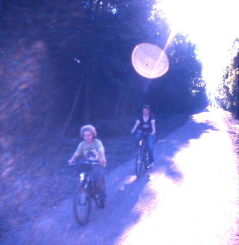 Kind und Mutter auf Fahrrädern im Gegenlicht auf der neuen Bahntrassen-Fahrradstrecke