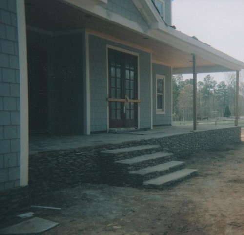 flagstone steps above thinly-stacked stonework under the front porch of home in Durham, North Carlolina
