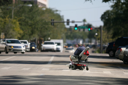 a person in a power chair crosses a pedestrian crossing on a tree lined street. our of focus cars are visible in the background, at a traffic light.