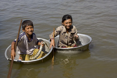 Two children with snakes in washtubs (Pondspider) Tags: lake water river children fishing cambodia vietnamese snake floating villages wash tub siemreap paddling snakes mekong sap coracle tonle anneroberts coracles sap annecattrell pondspider tonl