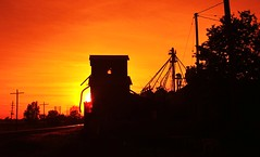 Sunset on Old Grain Elevator (chumlee10) Tags: railroad sunset colors wisconsin evening clinton sony tracks silhouettes wi grainelevator a300