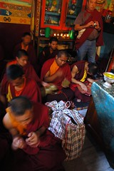 Plaid storage bag for ritual ornaments, green silk alter cover, upon sits a silver engraved offering vessel, plate metal and paper crowns, 5 Dhayani Buddhas, SteveD with a camera stands next to deity offerings, Boudha, Kathmandu, Nepal (Wonderlane) Tags: nepal religious buddhist buddhism tibetan kathmandu spiritual tantra esoteric boudha sakya tibetanbuddhism 6541 vajrayana lamdre plaidstoragebagforritualornaments greensilkaltercover uponsitsasilverengravedofferingvessel platemetalandpapercrowns 5dhayanibuddhas deityofferings