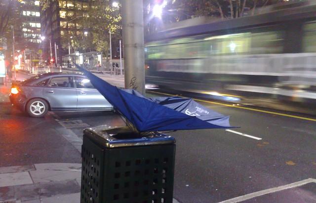 Broken umbrella in rubbish bin