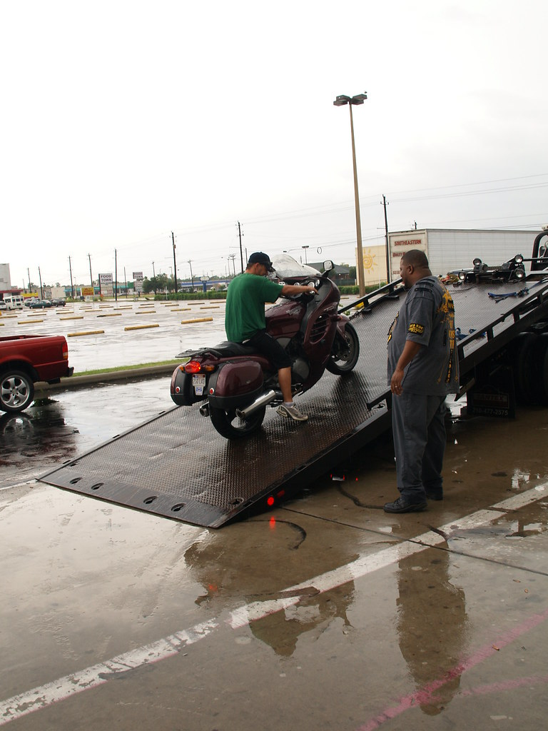 Pasadena Texas Motorcycle Shop 2010 Two guys unloading a motorcycle with a flat tire off a tow truck in the rain