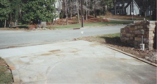 picture of flagstone laid into driveway with stone curbing on the left side under construction in Raleigh, North Carolina