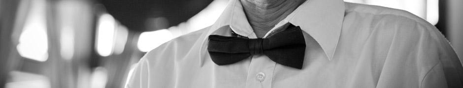 Fotografía en blanco y negro del cuello de un camarero, con su pajarita y todo