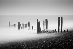 Skeleton Coast, Rye Harbour (flatworldsedge) Tags: longexposure sea white mist black fog skeleton drag coast waves harbour grain pebbles rye nets gravestones saltwater breakwater explored yahoo:yourpictures=blackandwhite yahoo:yourpictures=waterv2