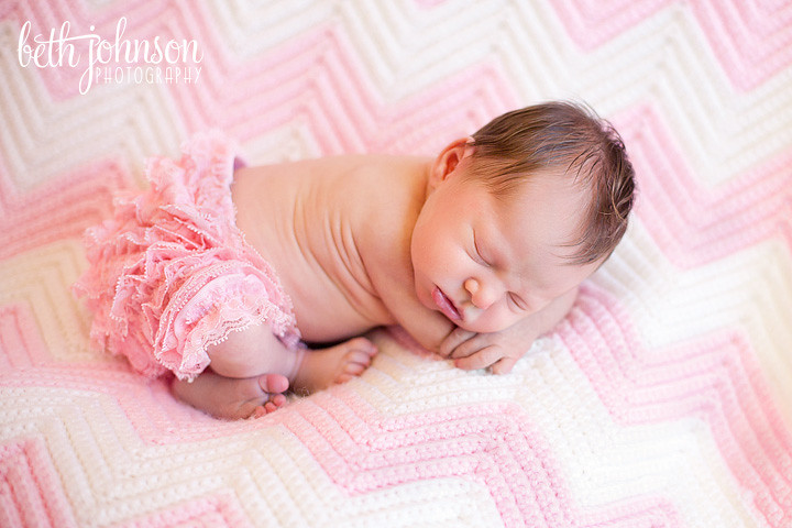 newborn baby on pink and white blanket