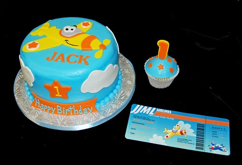 Airplane themed first birthday cake in blue orange and yellow