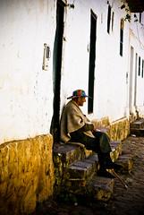 Old man in rana (poncho) - Villa de Leyva, Colombia (chris_esler2000) Tags: latinamerica southamerica colombia colonial oldman cobblestone spanish historical poncho oldarchitecture colonialtown boyacá