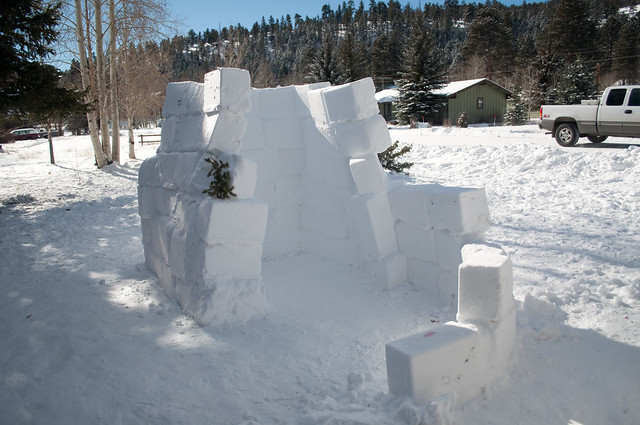 Half an igloo standing in the front yard, it has three big walls made of giant snow cubes and a tiny quarter wall on its way to winding around it in attempts to make a hallway. There is no roof on top and the walls are leaning in towards each other.