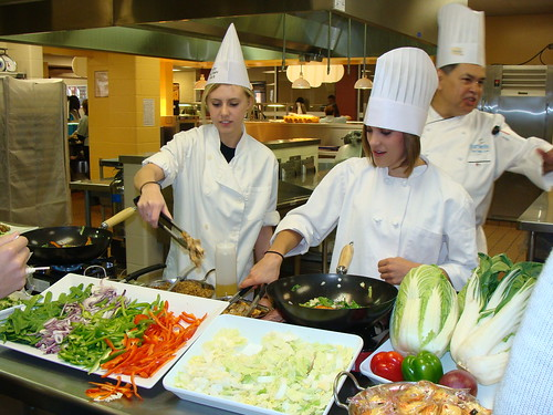 Smithson Valley High School culinary arts students Rachel Roff, left, and Emily Richardson, right, learn new cooking techniques from Chef Ralph Garcia.