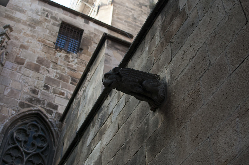 Photo of a gargoyle sticking out of a wall behind Barcelona's Cathedral