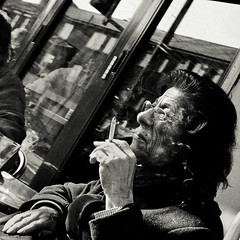 . (lazy_lazy_dog) Tags: uk portrait england blackandwhite woman reflection london window contrast digital canon square glasses sitting slow cigarette candid smoke grain streetphotography smoking thinking islington sevensisters 28mmf18 observing